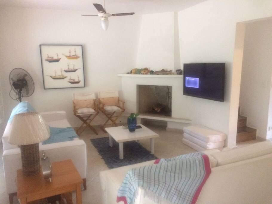 Sala com sofás e  cadeiras para 8 pessoas, TV 32 polegadas, 2 ventiladores e terraço com jardim