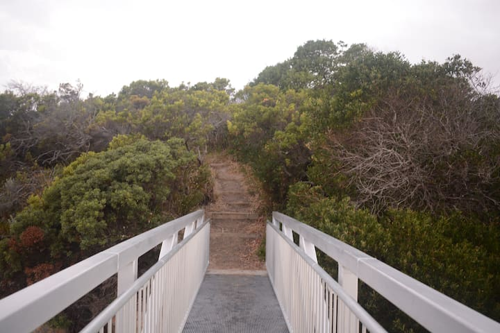 A bush track from the street leads down to a bridge giving access to the sand dunes