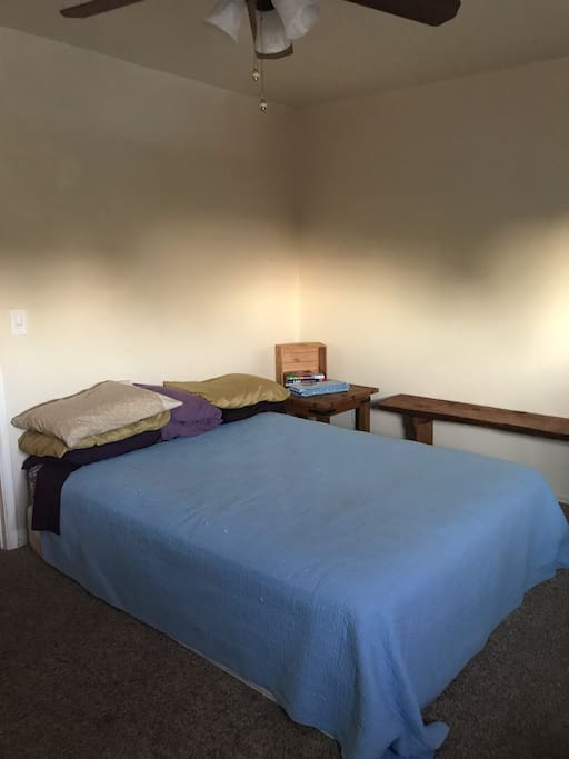 Cozy room with comfortable queen bed. Many pillows to choose from! Has space for luggage and a small desk for work.
