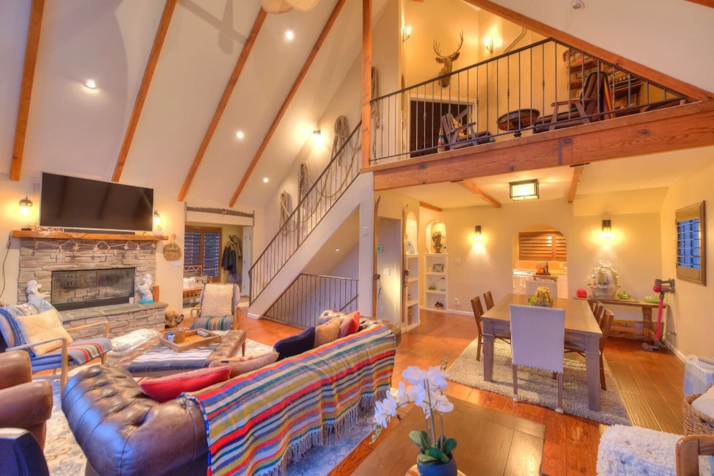 """View of the living room:  70"""" TV with direct TV, Apple TV and Firestick.  Dining room, upper level loft"""