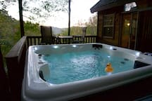 Deck with hot tub, seating, and view.