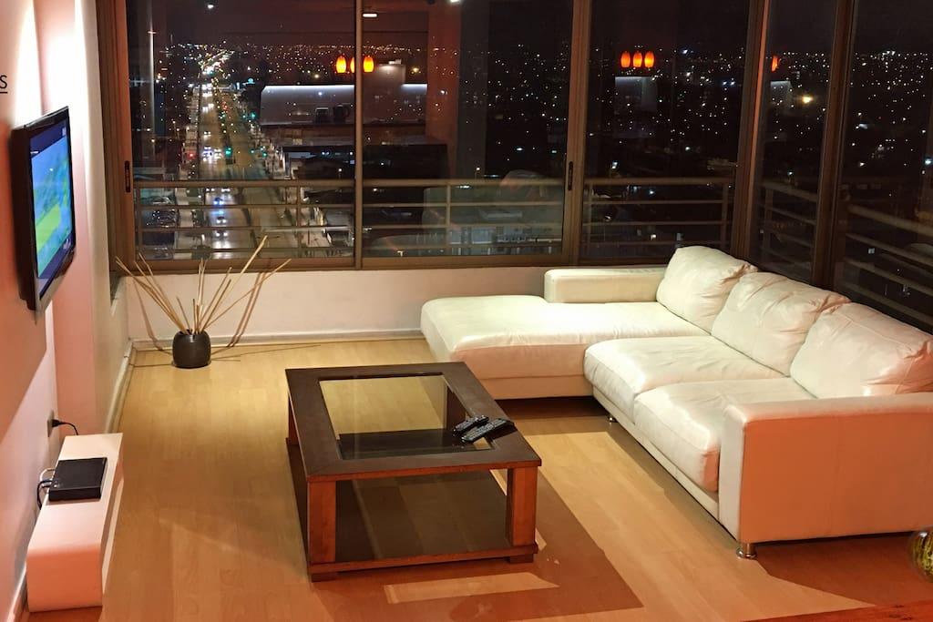 """Amplia  sala con vista panorámica de 270º, con cómodo sofá de cuero y TV LED de 40"""" con programación satelital HD, 32"""" en dormitorio principal."""