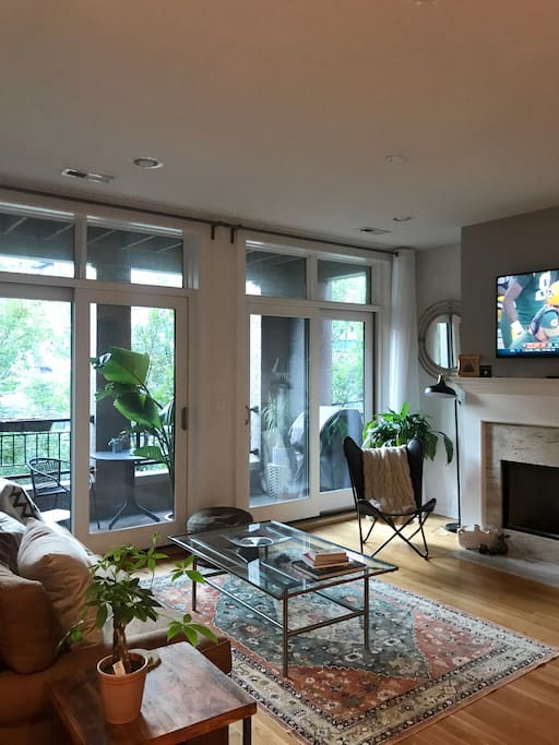 Living room with plenty of natural light, double door access to patio, cable TV, and gas fireplace.