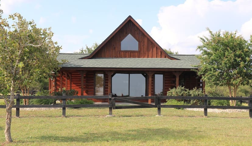 The Log Cabin is on a gated 47 acre ranch.  Enjoy panoramic views on 3 porches. The cabin is furnished with leather sofas, two bedrooms with comfortable bedding and adjoining baths, a sleeping loft with futons and a fully equipped upscale kitchen.