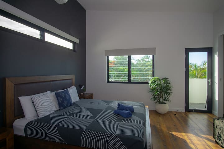 Upstairs master bedroom with king bed, A/C, TV, private balcony, ensuite and walk-in-robe