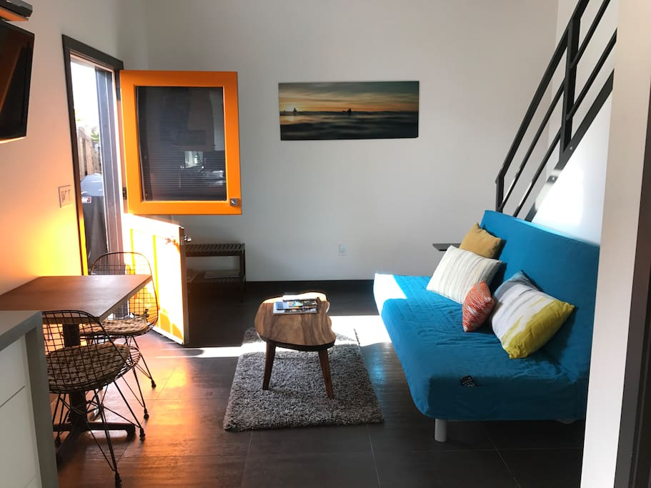 Hang out area. This couch turns in to a full size bed, also an orange dutch door leading out to a patio with BBQ & seating.