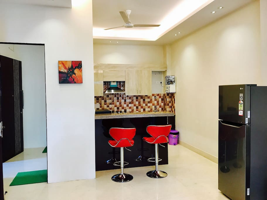 View of Kitchen & Dining Area with Stovetop, Refrigerator, Microwave, Crockery & RO Water Purifier