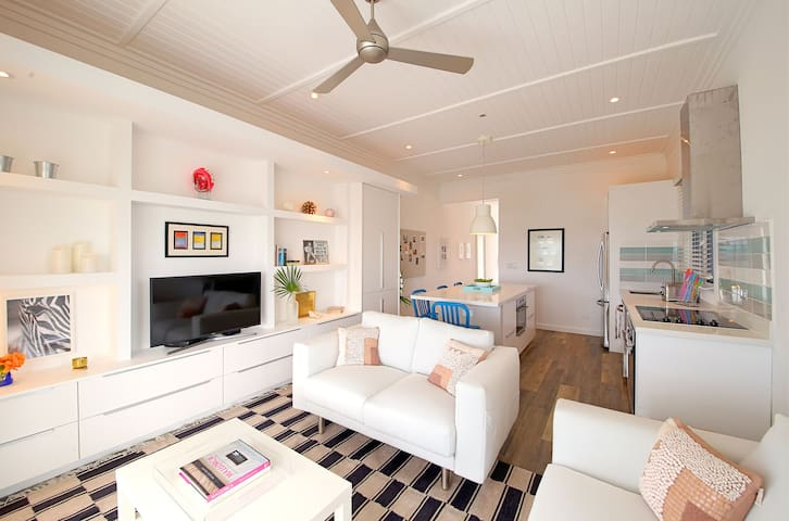 The apartment is furnished with clean, modern decor creating a bright and airy living space