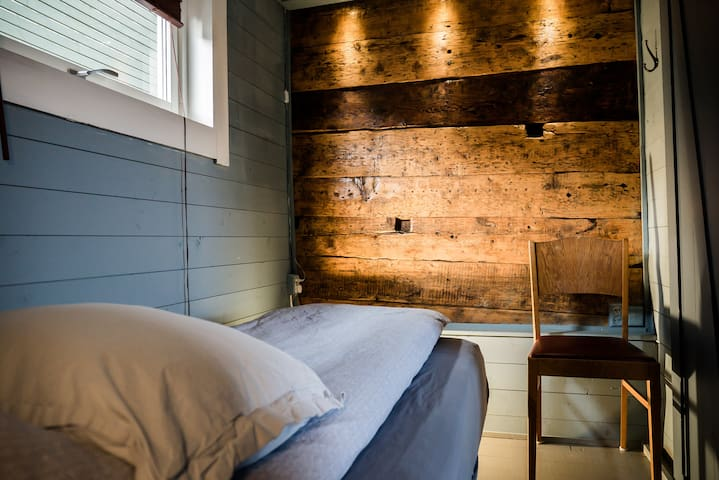 Bedroom 3  - with a window and original timber wall.