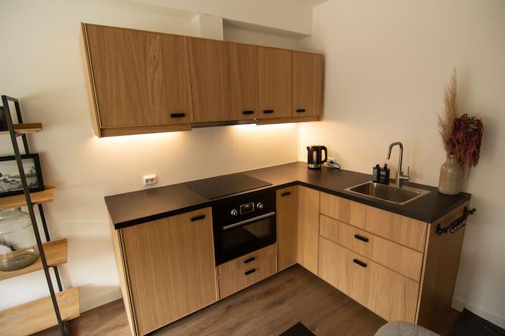 De keuken met oven, koelkast en 4 pits-kookplaat biedt de mogelijkheid om uitgebreid te koken.