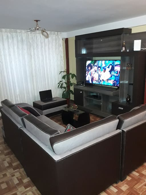 Spacious and comfortable living room with widescreen TV.