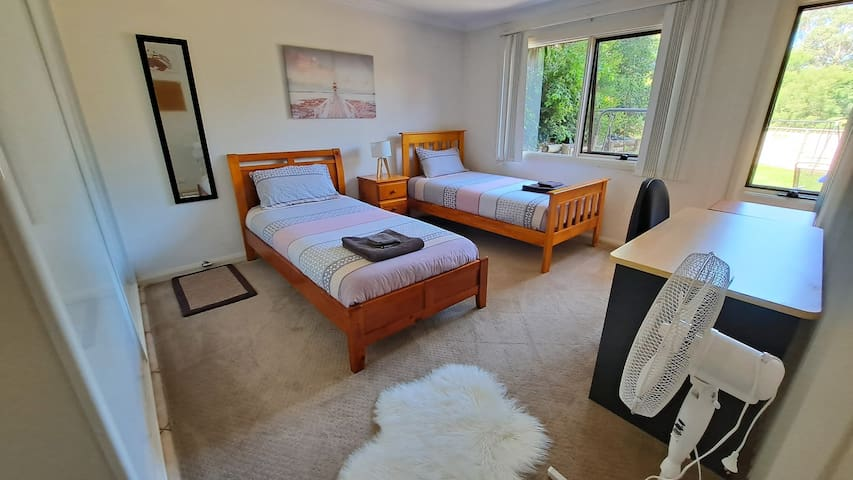 Beautiful and spacious bedroom with 2 single beds, a large wardrobe with plenty of coat-hangers, an iron, iron board and a study desk for your use  complimented by the lovely garden outlook. There is unlimited wifi in the accommodation.