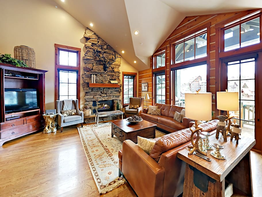 The living room features stately vaulted ceilings, natural log walls, and an impressive floor-to-ceiling stone fireplace.