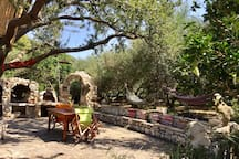 Vounaki stone yard and its arched entrance - Traditional stone BBQ and oven in the background