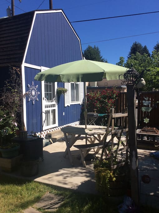 Yard has table with umbrella and seating.