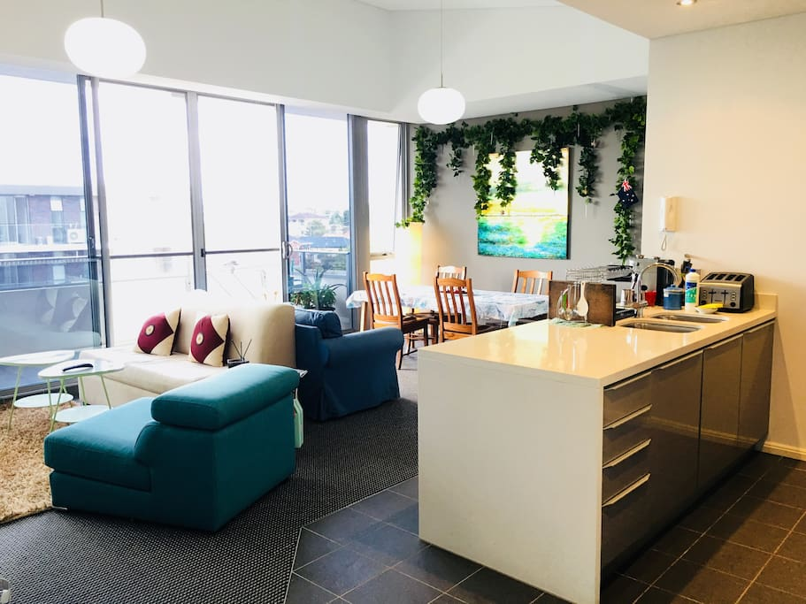 Lounge room and dining area, it's an open space, you can access our balcony and kitchen. All this area is just next to floor to ceiling windows! This picture is taken from the door way. 客廳和餐桌區,就在陽台跟廚房旁邊,整個空間旁邊就是落地窗!這張照片的角度是從走廊看過去。