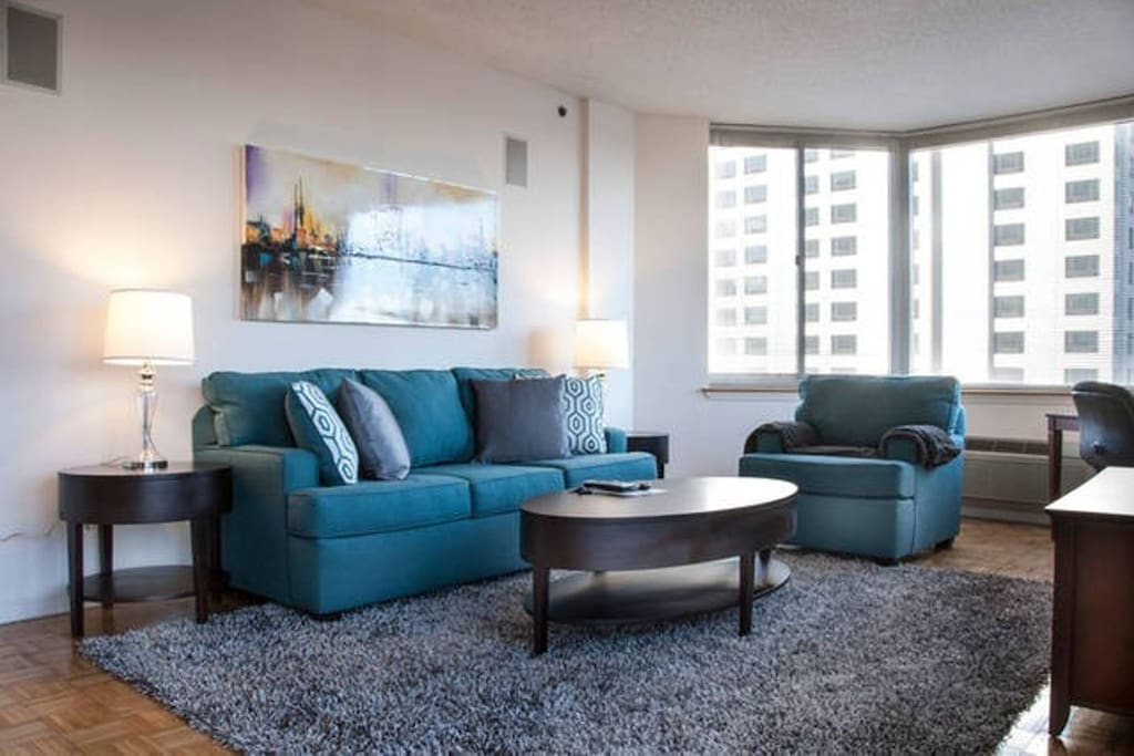 Comfortable living room with pullout sofa bed, club chair and over-sized windows providing a lot of natural light