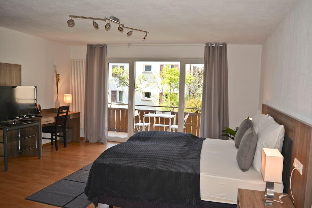 Schlaf-, Wohn- und Arbeitsbereich mit Blick auf großem Balkon