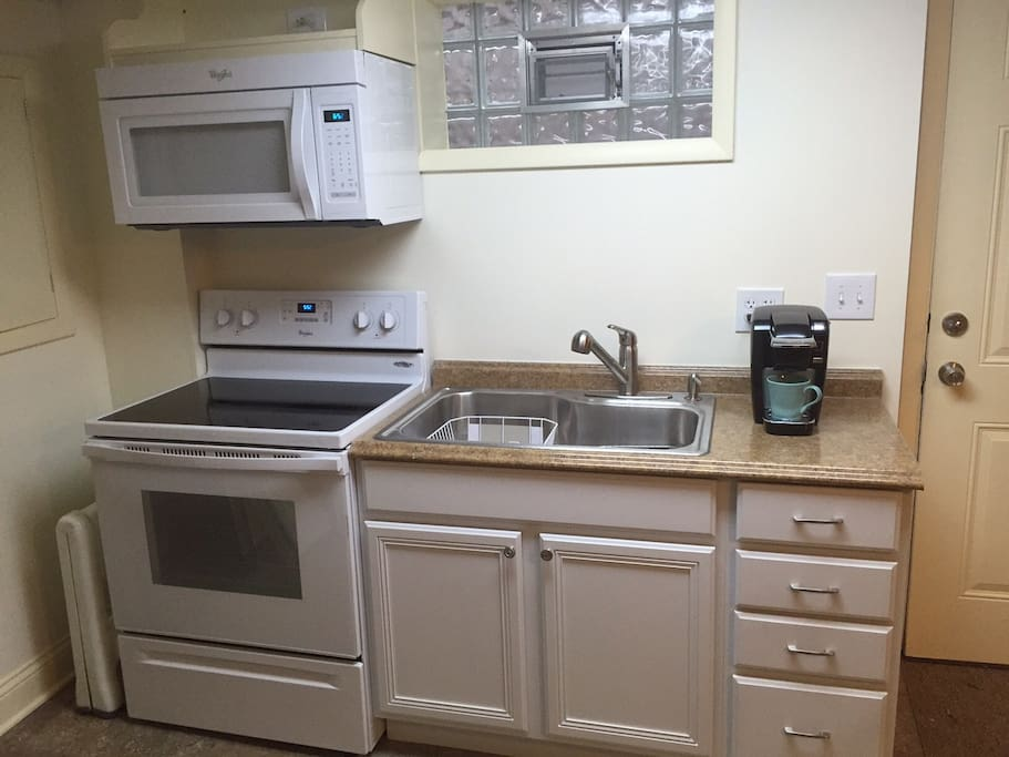 Kitchenette with basic cooking supplies and small refrigerator