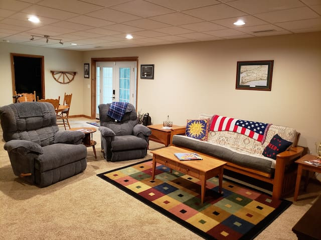 The large living area includes a futon sofa sleeper (full size bed), two recliners, and end tables along with a 47 inch flat screen TV, Blu-ray player, and electric fireplace.
