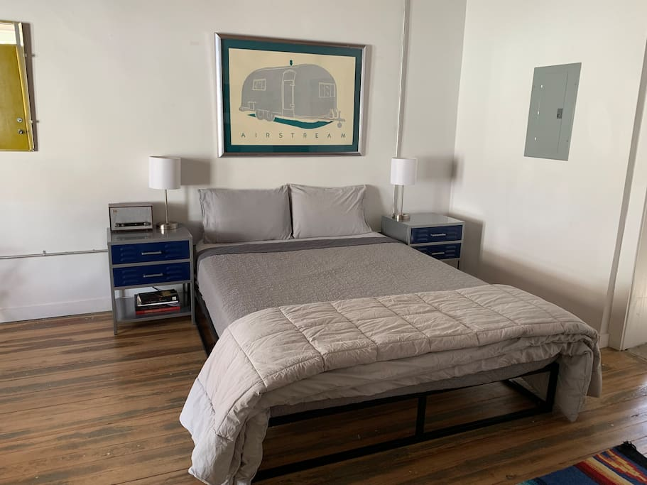 Queen-size bed with nightstands and art