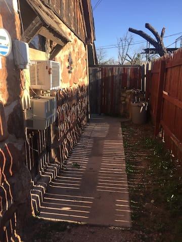 Behind fence, follow sidewalk to rear entry door.
