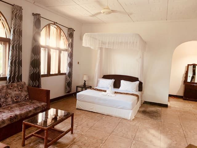 Large private room with mosquito nettings, large windows, tv and seating area