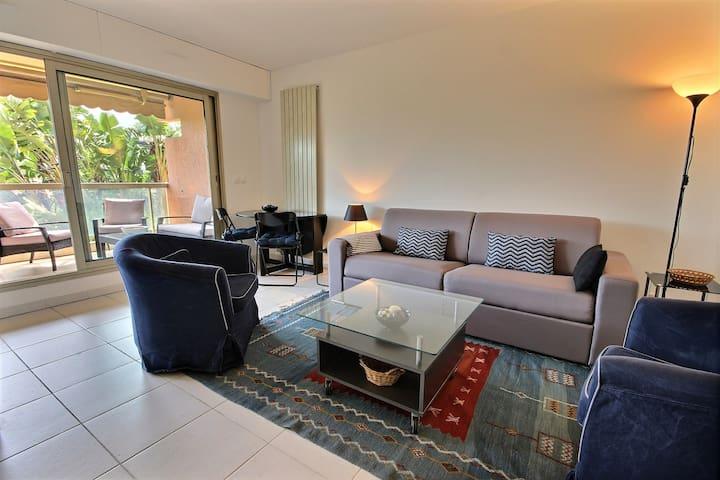 Salon donnant sur terrasse équipé d'un canapé lit, 2 fauteuils et d'un espace repas.