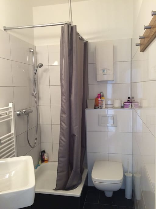 Gepflegtes Badezimmer mit Dusche und gut ausgeleuchtem Spiegel.