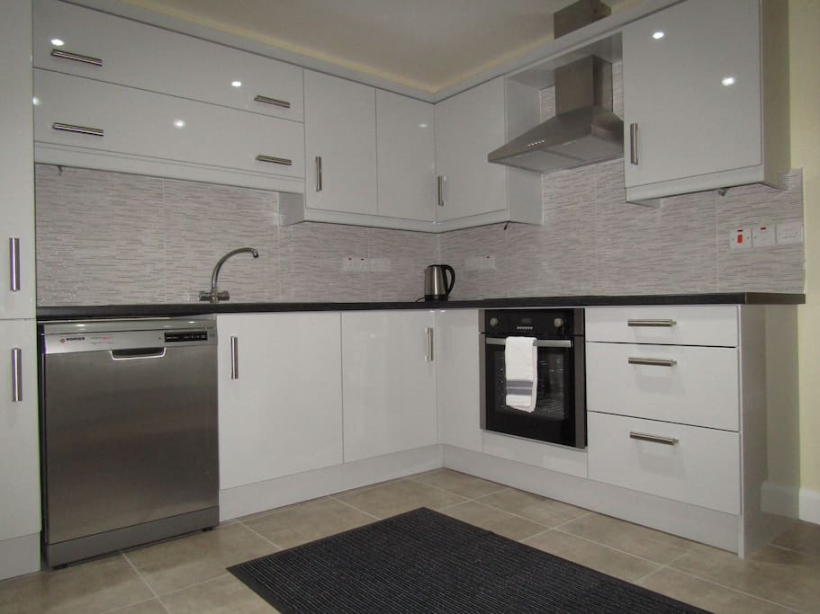 Kitchen in apartment, with dishwasher, large fridge-freezer, kettle and cutlery plates etc