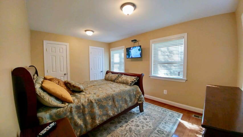 Bedroom with queen-size bed, TV mounted on wall with Verizon Fios.