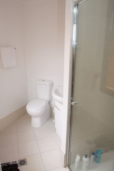 Clean bathroom comlete with shower, toilet and vanity