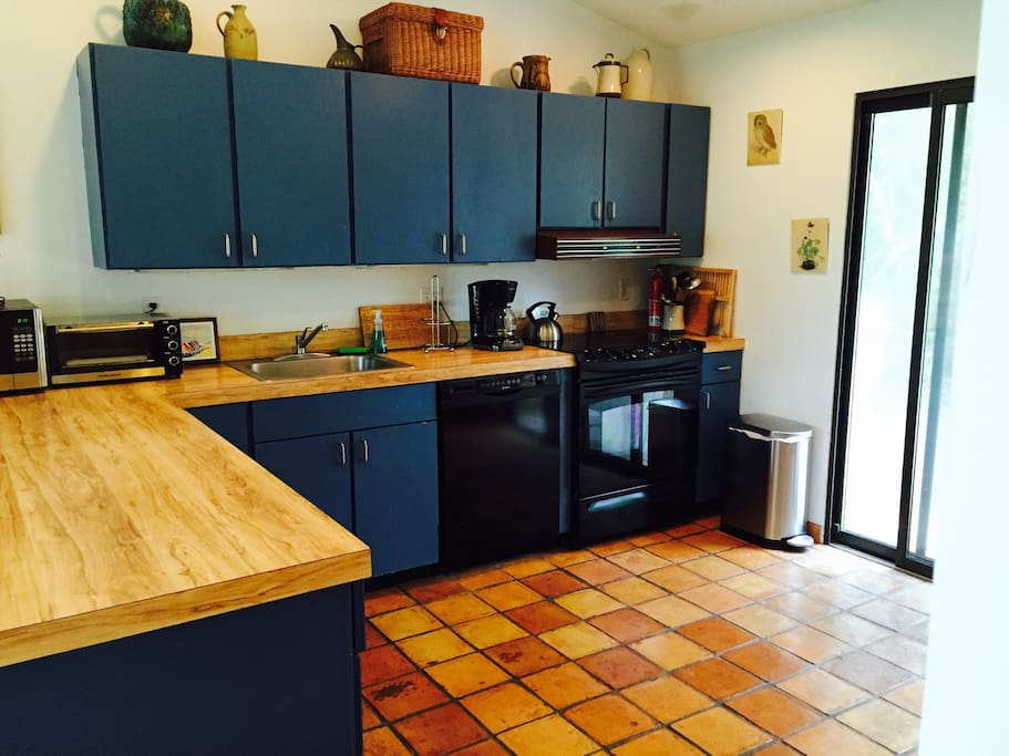 Fully equipped kitchen opens to walkway and garden