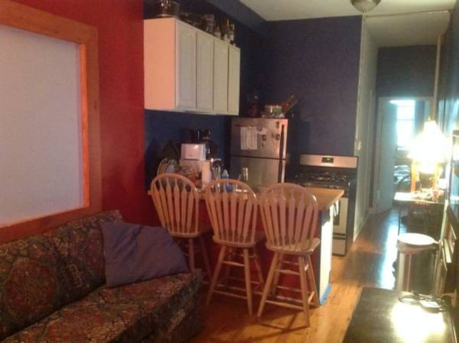 Kitchen includes: microwave, coffee machine, freezer/refrigerator, stove/oven. Three chairs face the kitchen island like a bar. Comfortable couch faces the TV.