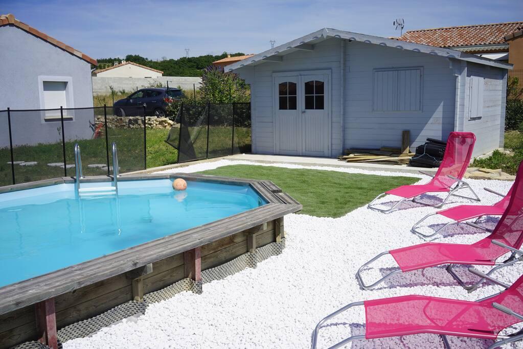La piscine et l'abri piscine, la maison sur la gauche