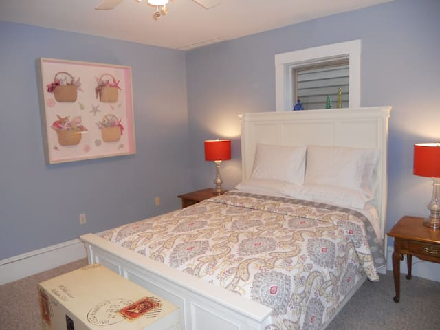 Comfortable queen bed with many pillows.