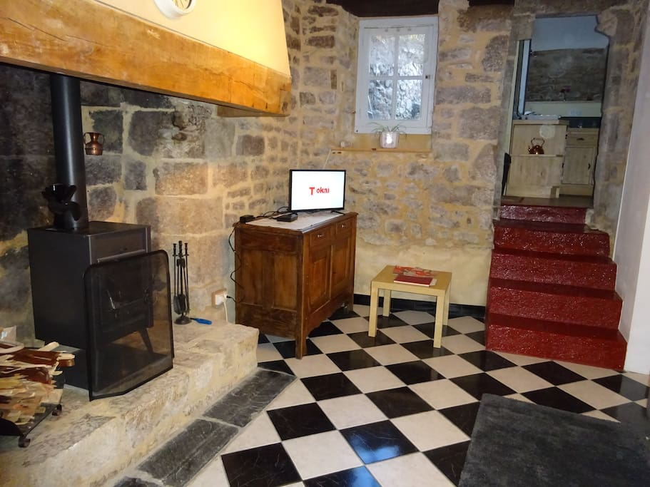 Breton fireplace, antique sideboard and steps up to kitchen