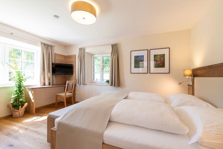 Top 1 - Ferienwohnung Zaunkönig. Schlafzimmer mit Doppelbett 180x200 cm, Schreibtisch, Smart TV, Schrank und Spiegel.