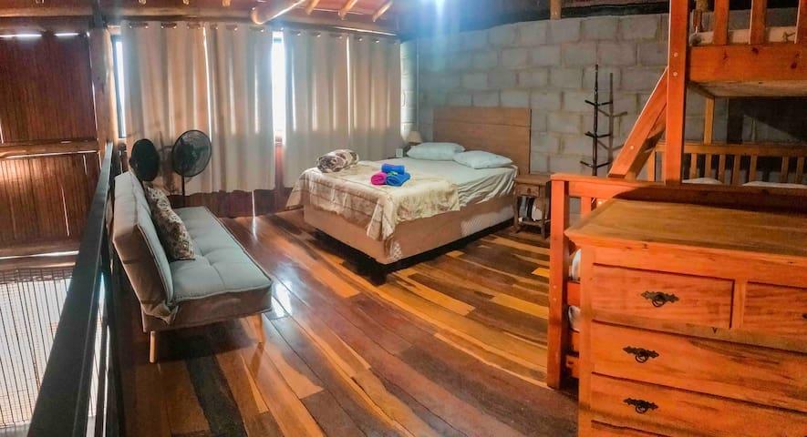 Quarto da Casa da Serra: possui uma cama de casal, uma triliche (uma cama de casal, e duas camas de solteiro) e um sofá-cama dobrável, ao todo são 8 lugares para dormir no quarto.