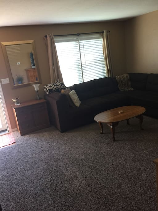 Living room with large comfy sectional couch with xfinity cable TV and internet