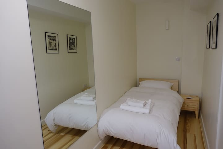 Bedroom 3 on 2nd floor. A long narrow room with a single bed at either end.