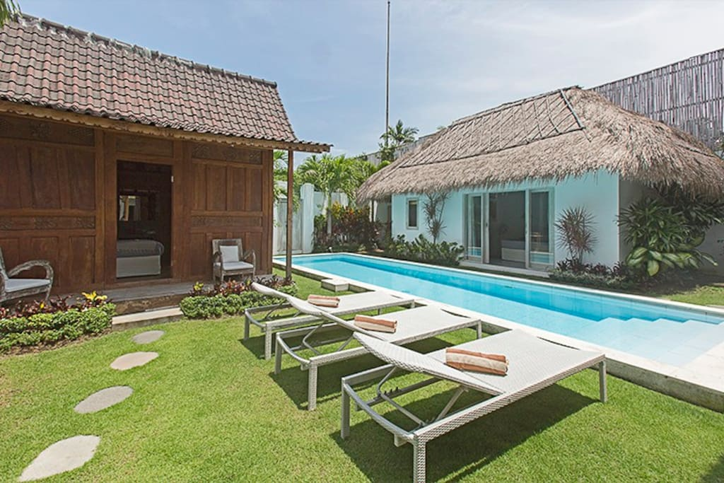 Sun chairs by the pool with the bungalow room in front