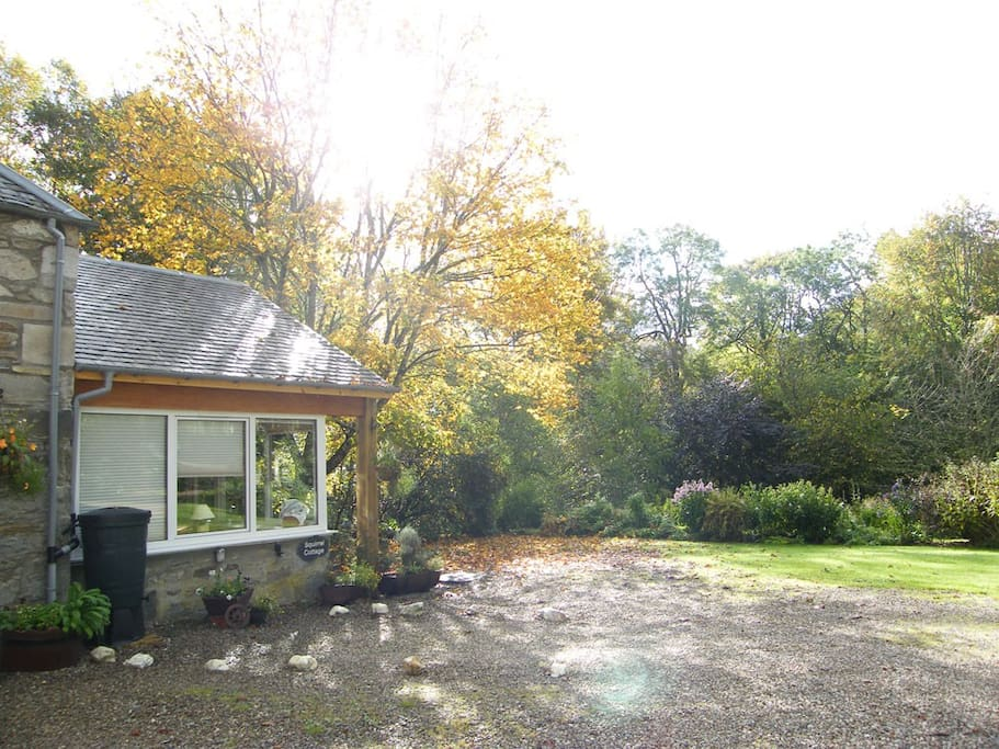 Side view of Squirrel Cottage sun room with the garden in front. Plenty of Car Park space.