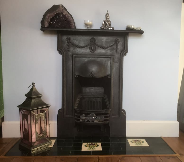 Restored, decorative cast iron fireplace with calming crystals.