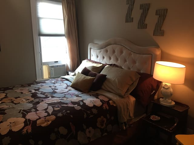 Queen bed with AC unit.