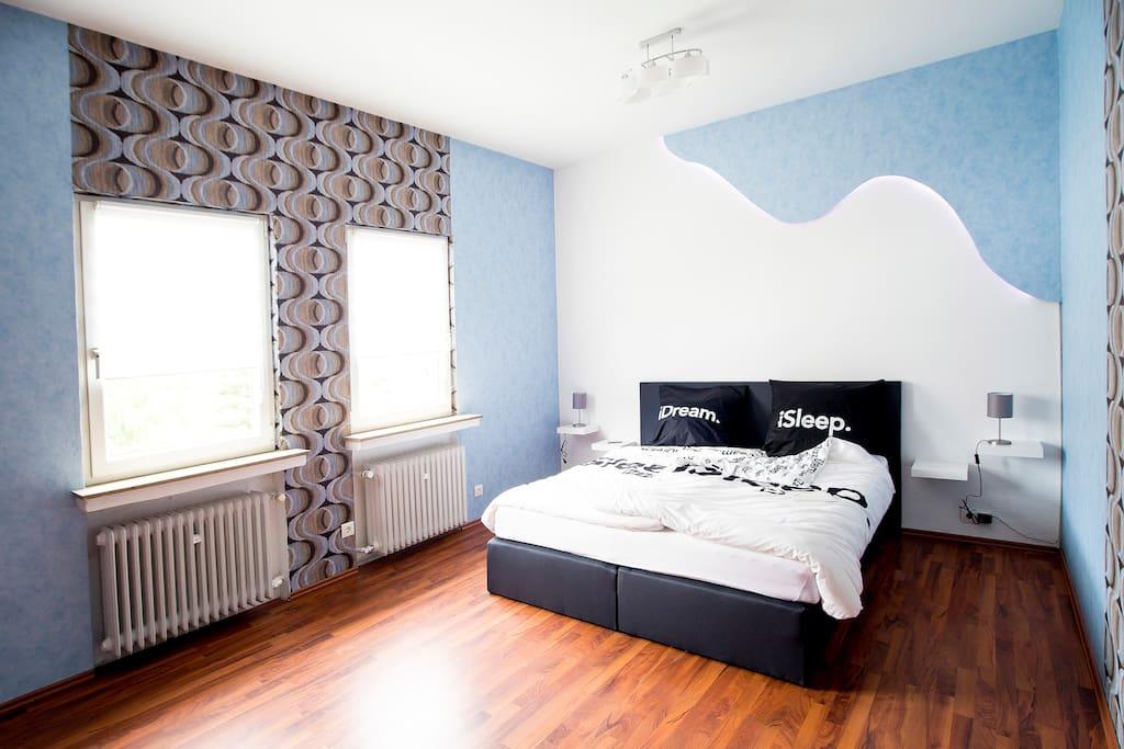 Schlafzimmer mit aktuellem Boxspringbett und entspannender LED-Beleuchtung.