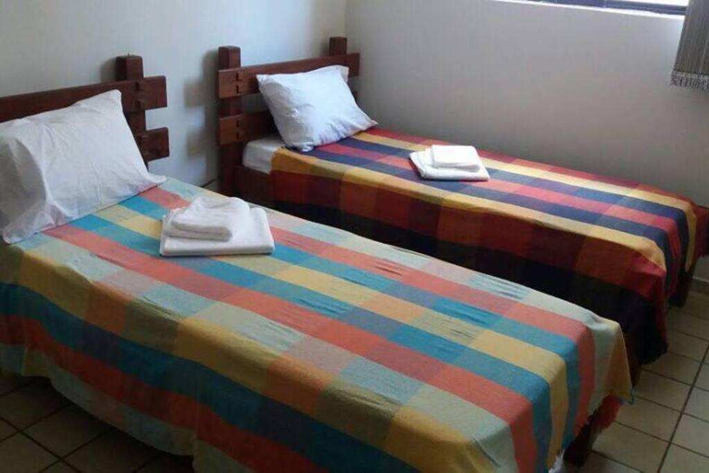 Segundo quarto com split, duas camas de solteiro, camiseiro e 1 sofá cama.