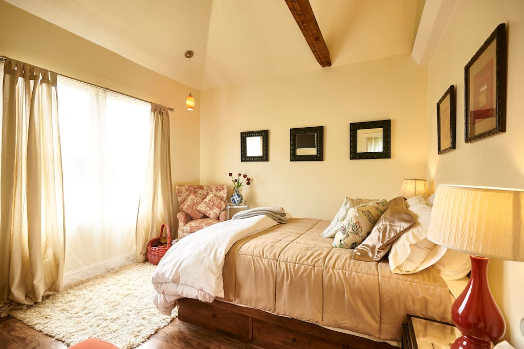Bedroom 1: Queen bed, High ceiling and sun shines through the window at front of the house