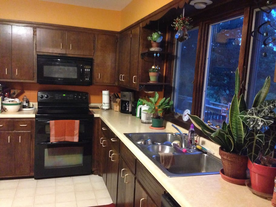 Shared kitchen area with microwave, dual oven, refrigerator access, and dishwasher