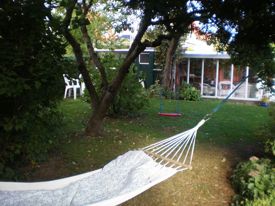 Hængekøjen mellem frugttræer og udestue/drivhus i baggrunden